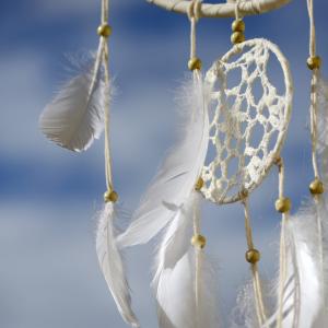 mindfulness for better sleep. white dream catcher set against a blue sky.